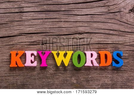 keywords word made from colored wooden letters on an old table. Concept