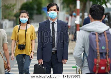 Asian businessman in protective mask looking at camera seriously while standing against pedestrian crossing