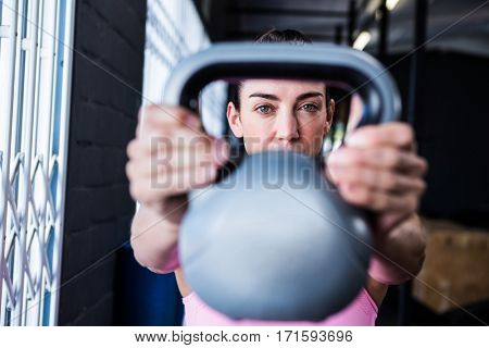 Portrait of serious female athlete lifting kettlebell in gym
