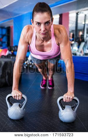 Portrait of serious female athlete doing push-ups in gym