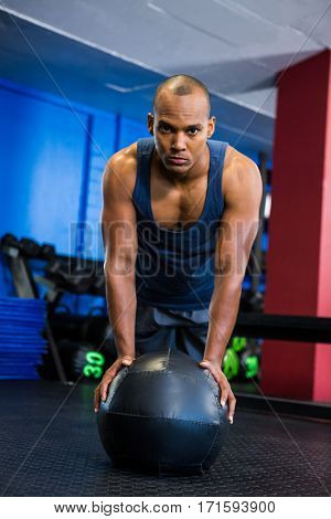 Portrait of serious athlete with fitness ball while exercising in gym