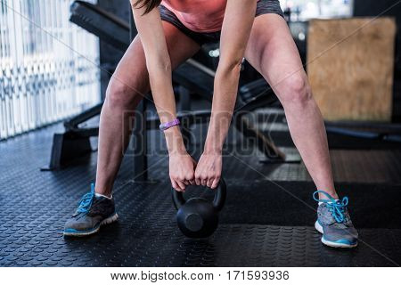 Low section of athlete holding kettlebell while exercising in gym