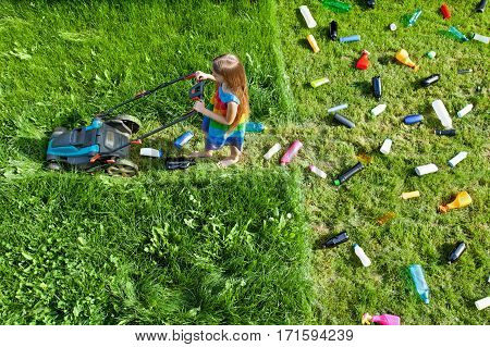 Pollution concept with little girl using plastic spewing lawn mower leaving litter behind