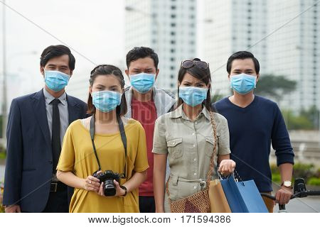 Asian people looking at camera with dissatisfied face expressions while suffering from air pollution in city center