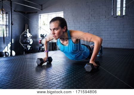 Sporty young woman holding dumbbells while exercising in gym