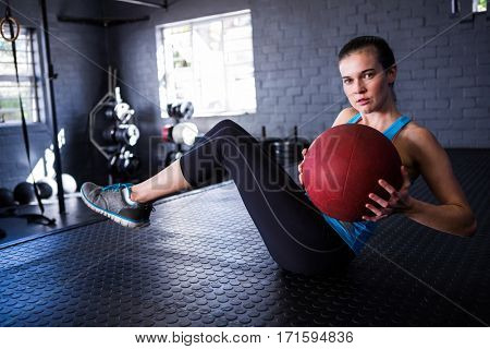 Portrait of young athlete holding exercise ball in gym