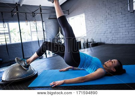 Female athlete with BOSU ball while exercising in gym