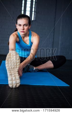 Portrait of young woman stretching while sitting in gym