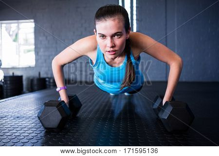 Sporty woman doing push-ups with dumbbells in gym