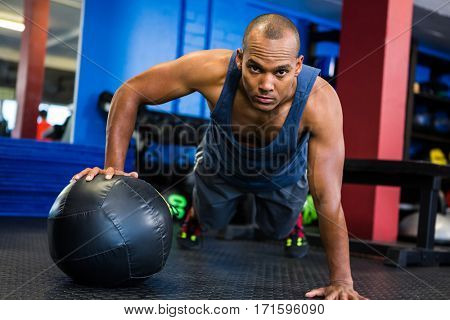 Portrait of serious man doing push-ups with exercise ball in gym