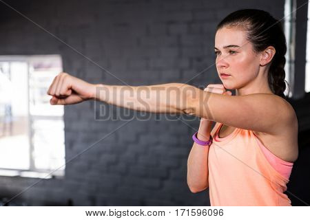 Young woman punching while standing in gym