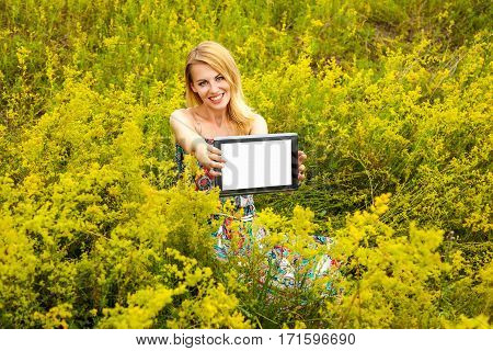 Girl doing selfie. Beautiful blonde in white-red dress does selfie in the field on her phone. The girl in the field with the phone the girl makes self the girl with the tablet a girl with headphones girl listening to music