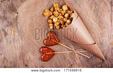Two lollipop in the shape of a heart and a paper bag of caramel popcorn on wooden background. Fast food and unhealthy food.