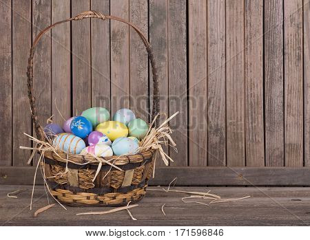 Colorful Easter eggs in a basket on a wooden surface