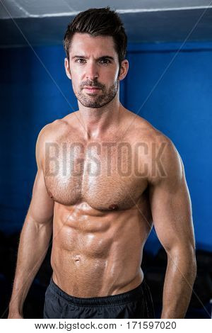 Portrait of shirtless male athlete standing in gym