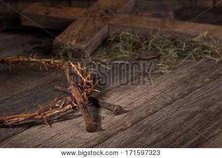 Crown of thorns and nails with a cross in background on a wood surface