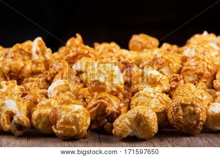 Golden caramel popcorn closeup. Background of popcorn. Unhealthy food
