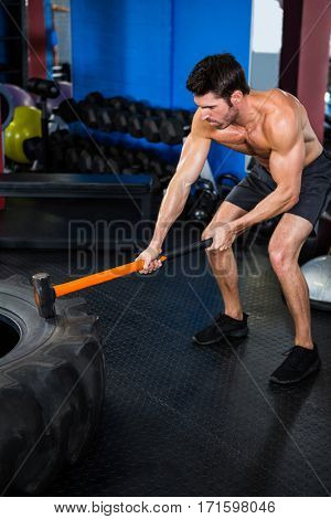 Shirtless male athlete exercising with sledgehammer in gym