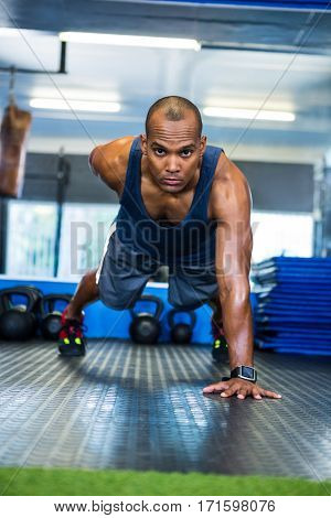 Portrait of serious male athlete doing push-ups in gym