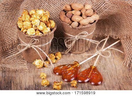 Paper bucket of caramel popcorn roasted peanuts in shell and lollipops. Set meal for a movie. Not healthy food and snacks