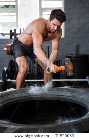 Determined male athlete exercising with sledgehammer in fitness studio