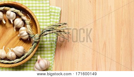 Braid of garlic in wooden plate on a fabric green plaid cloth on a light wooden table.