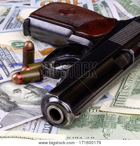 Pistol with bullets on the banknotes of American dollars crime or corruption concept.