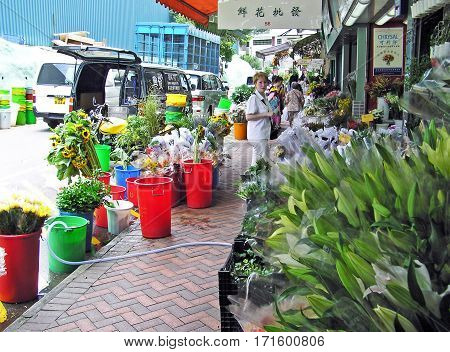 Hong Kong, China - March 23, 2003: People stroll through the flower market in Hong Kong for shopping. On the sidewalk and the street many colorful flowers are in water containers. The road is blocked by delivery vehicles.