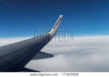 Girona, Spain - September 23 2016: Ryanair wing tip on aircraft over clouds. Day view of wing tip with Ryanair logo shot inside window of flying aircraft Boeing 737 800.