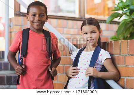 Portrait of smiling school kids standing on staircase at school