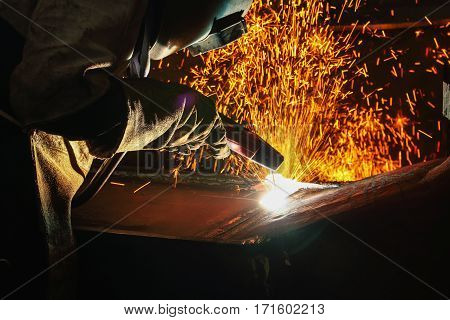 Welder arc Gouging carbon electrode rods with sparks and smoke in factory
