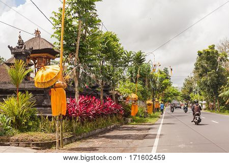 UBUD INDONESIA - January 26 2013. Religious decoration near houses on street. Road traffic in sunny day.