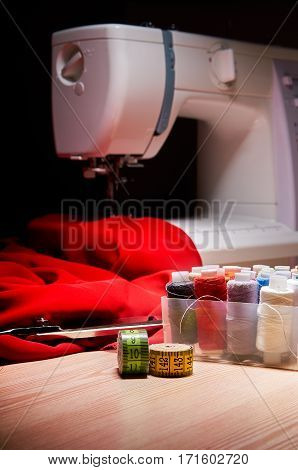 Workplace seamstress. Sewing machine and sewing supplies on the black background.