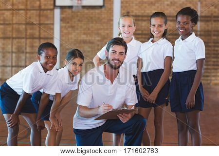 Portrait of sports teacher and school kids in basketball court at school gym