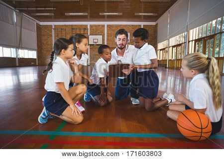 Sport teacher and school kids discussing on clipboard in basketball court at school gym