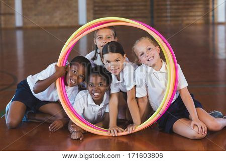 Portrait of school kids looking through hula hoop in basketball court at school gym