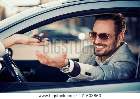 Car dealership.Young man receiving car key from saleswoman.