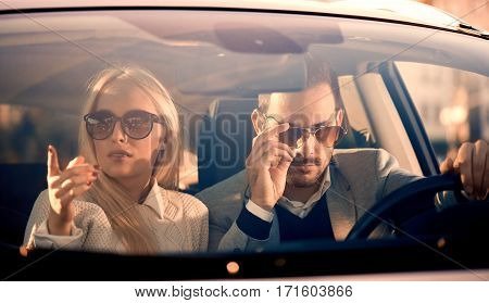 Young couple together in car - man drivingenjoying together.
