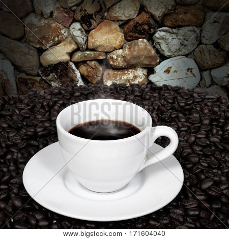 Black coffee in cup and coffee beans with smoke on stone wall background.