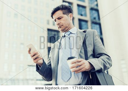 Close up portrait of a successful businessman using a smart phone while standing by a modern office building.
