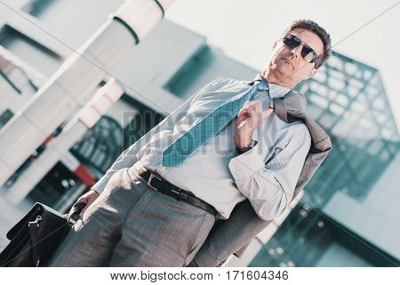 Portrait of confident businessman while standing by a modern office building.