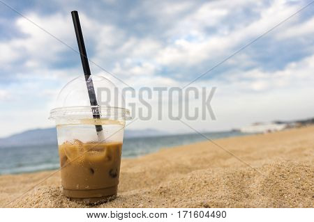 glass with black straw iced coffee is in the sand on the seashore.