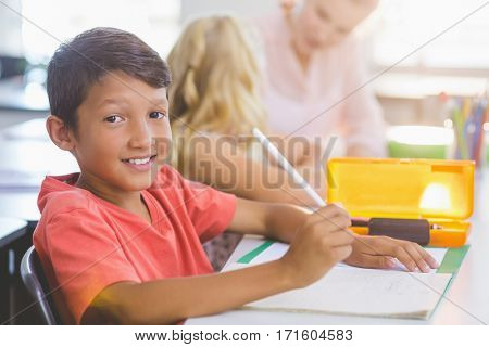 Portrait of schoolboy doing his homework in classroom at school