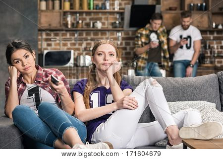 Young upset women sitting on sofa and watching tv at home