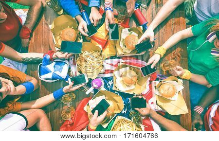 Barbeque supporters party around table holding phone - Top view of fast food lunch table with people using mobile as modern lifestyle and technology addiction concept - Vintage nostalgic filter look