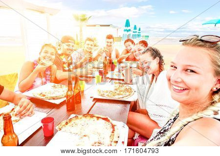 Big group of friends pizza party selfie on beach bar restaurant at sunset - Happy teenagers having fun on vacation at dinner with drinks and food on table - Sun halo filter focus on right third girl