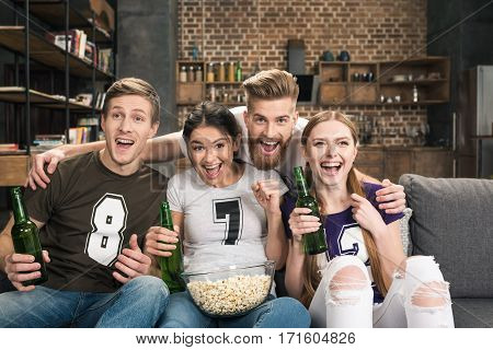 Excited young friends in t-shirts drinking beer and eating popcorn at home