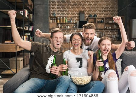 Excited young friends drinking beer and eating popcorn while supporting favorite team at home