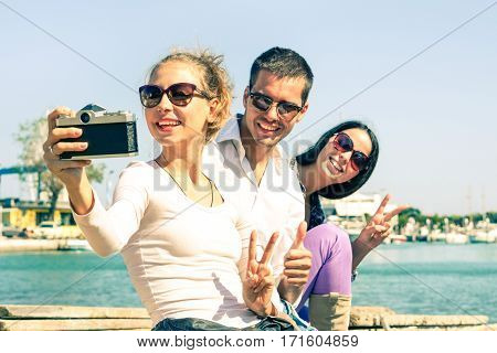Happy best friends taking selfie with vintage camera at pier - Cheerful students on vacation having fun doing photo by the ocean - Concept of joyful moments with attractive playful teenagers outdoors