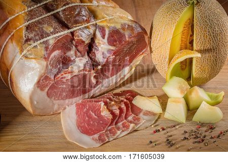 Beef steak with spices and seasonings and sliced pieces of yellow melon. A big piece of meat. Steak. Grill beef steak. Traditional Italian appetizer parma ham with melon - prosciutto melone.